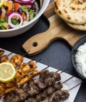 Greek Feast with Wine or Beer for Two ($39) or Four People ($78) at King Jon's Souvlaki Bar (Up to $150 Value)