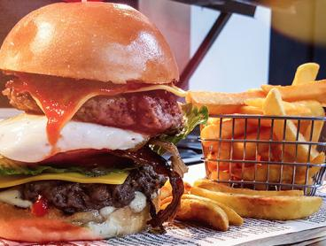 Scrumptious Burger with a Beer or Soft Drink Each - $22 for Two People or $39 for Four People (Valued Up To $90)